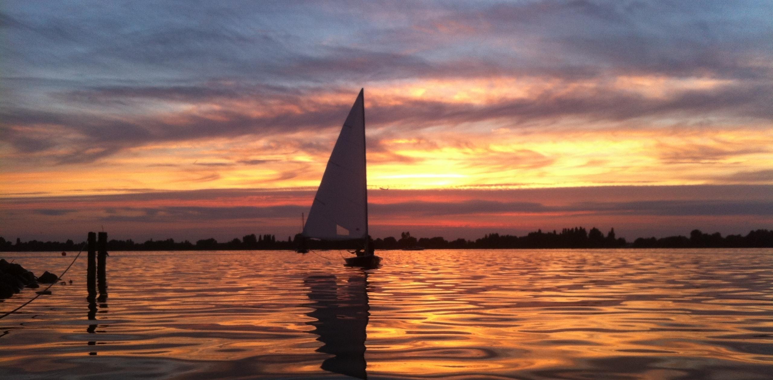 Een Laser is 's avonds aan het zeilen, op de achtergrond is een prachtige zonsondergang te zien.